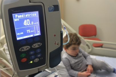 Infusion pump in sharp focus with Pudding on hospital bed behind.