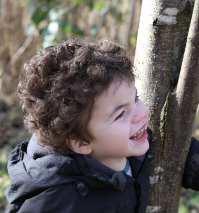 Pudding peering around a tree with a huge cheeky grin.