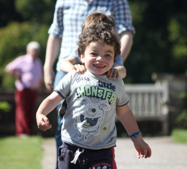 Pudding running towards camera. His big brother is behind him with hands on his shoulders.