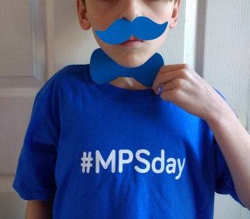 Boy wearing #MPSday t-shirt with a blue paper bow-tie and moustache