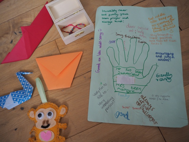 Origami, a little wooden chest with a friendship bracelet in, a toy monkey, and a picture of a hand with lots of nice comments written on.