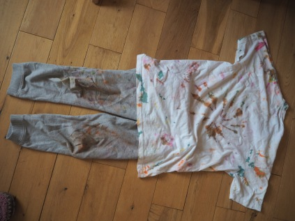 A tie-dyed T-shirt and some trousers covered in face-paint