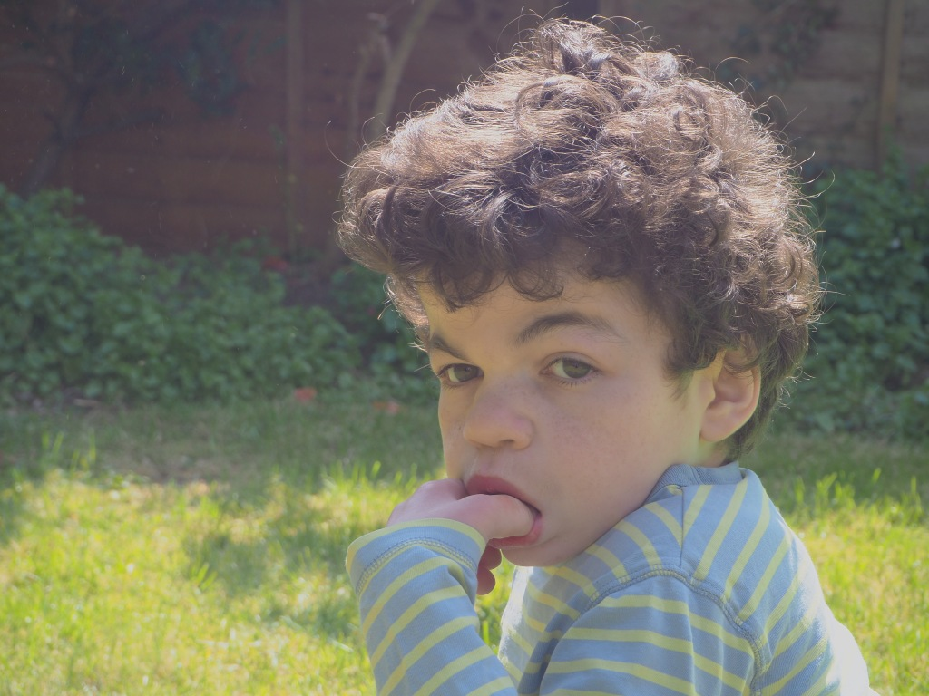 A close up photo of boy with curly hair with his thumb in his mouth. He is not smiling.